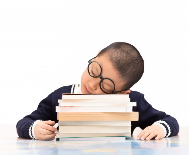 schoolboy-sleeping-on-school-books_1127-328