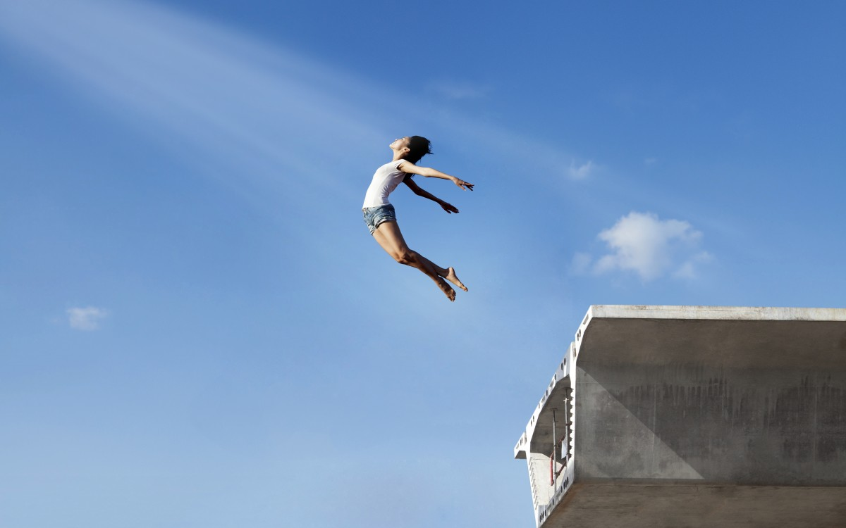 Asian woman flying off the bridge. Shot over clear blue sky.