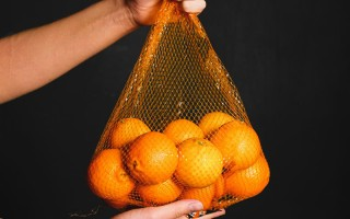 a-fresh-orange-inside-of-a-fruit-net-3683206