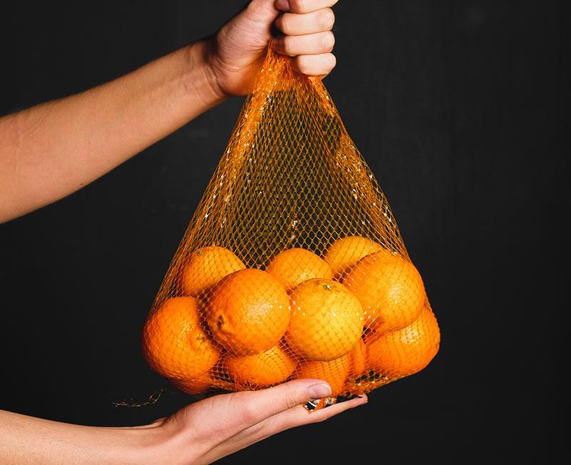 a-fresh-orange-inside-of-a-fruit-net-3683206